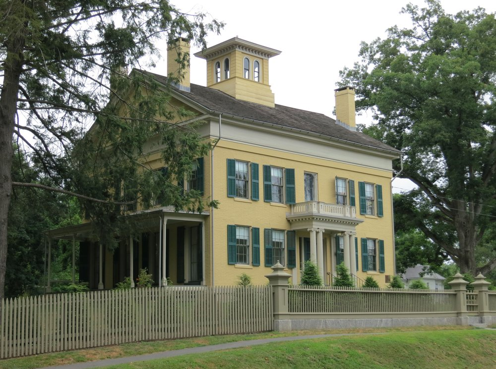 A photograph of a two-story Georgian house with yellow brick and green shutters. There are two chimneys, a cupola, an elaborately pedimented doorway, and a shady veranda. The house is surrounded by green trees, a hemlock hedge, and a tan, wooden fence.